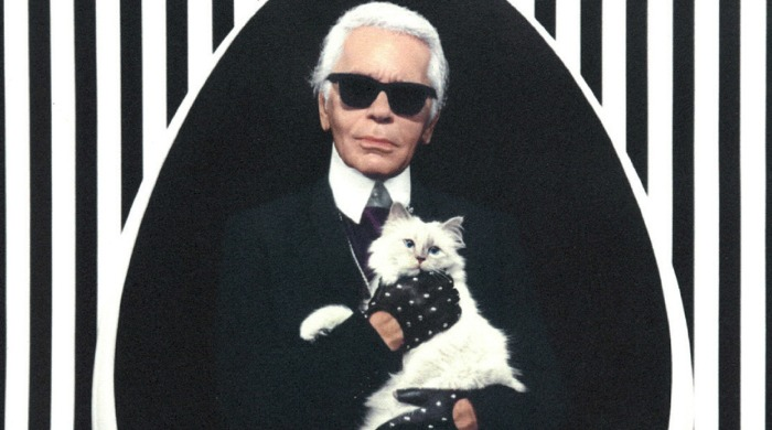 Karl Lagerfeld holding Choupette with a black and white striped background.