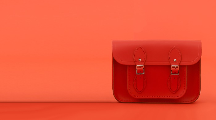 A red Cambridge Satchel Company bag against a red background.