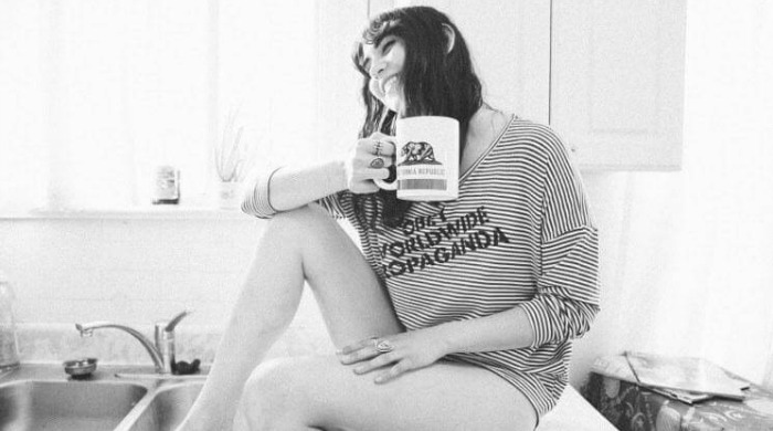 A model wearing a striped OBEY jumper holding a mug.