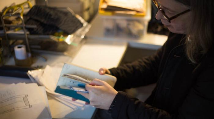 YMC Designer Fraser Moss at a desk looking through a notebook.
