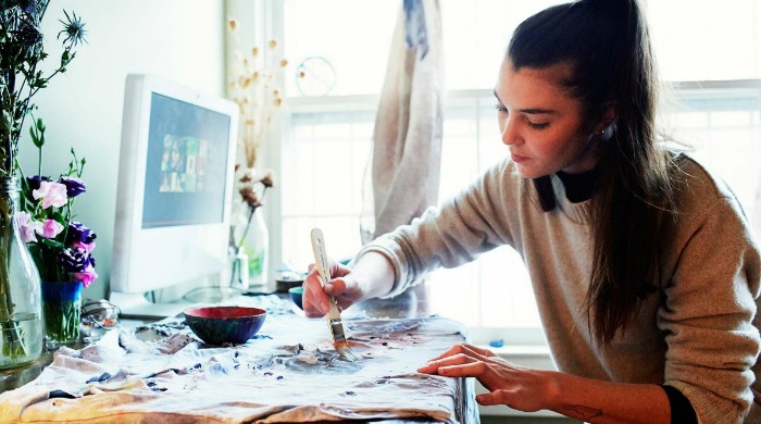 Audrey Louise Reynolds painting at a desk.