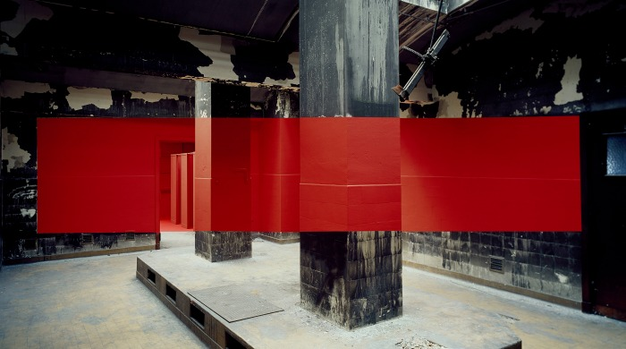 A large red rectangle across the middle of an industrial room by Georges Rousse.