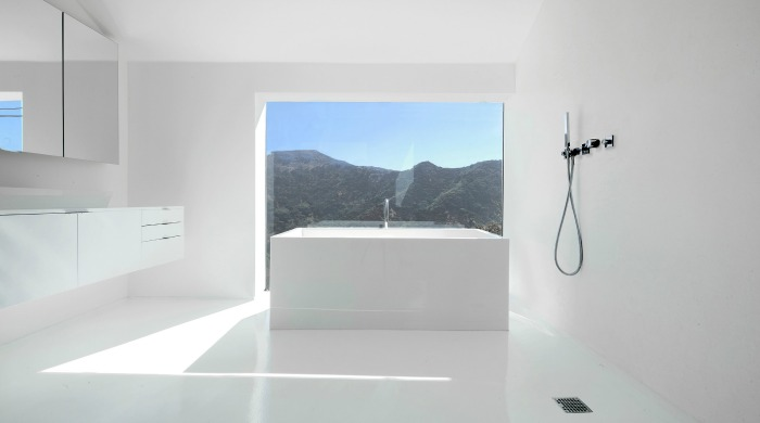 A white bathroom in the Nakahouse with a view of the hills.