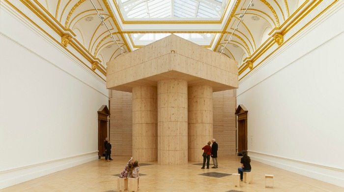A wooden structure in a large exhibition space at the Royal Academy of the Arts.