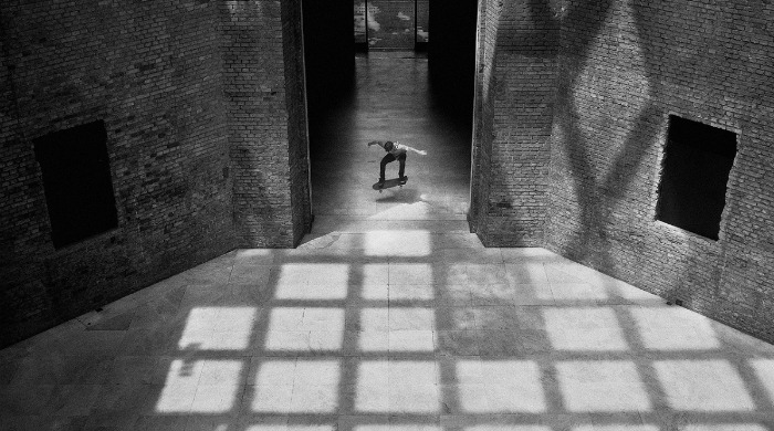 Fabiano Rodrigues  skateboarding inside a large brick building.