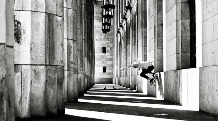 Fabiano Rodrigues skateboarding down a corridor with large columns.