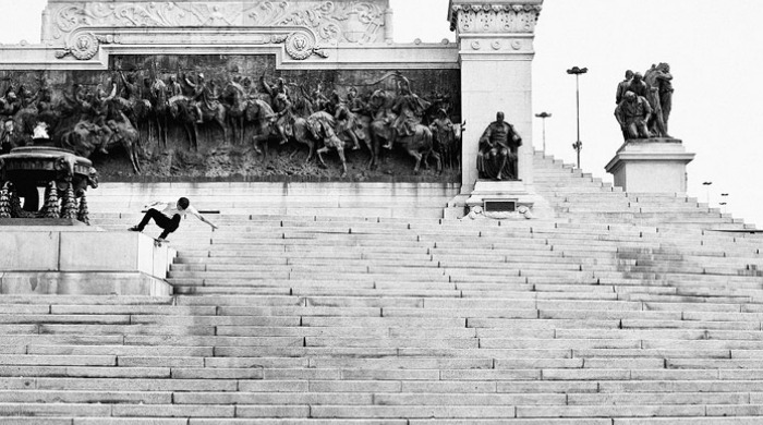 Fabiano Rodrigues  skateboarding on a set of stone steps.