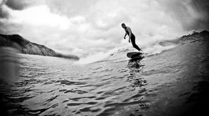 A surfer on a surfboard by Blank Surfshack.
