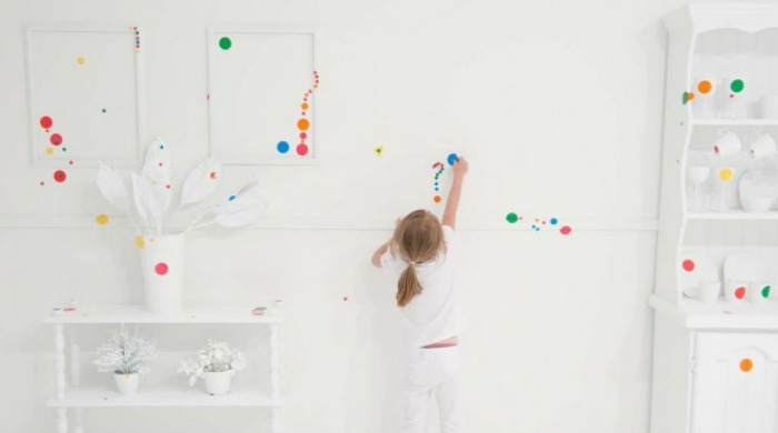 A child placing a sticker on the wall of the Obliteration Room by Yayoi Kusama.