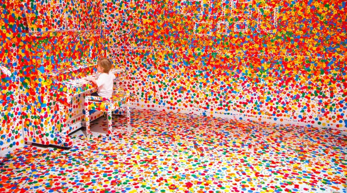 A child at a piano in the Obliteration Room, covered with colourful stickers by Yayoi Kusama.
