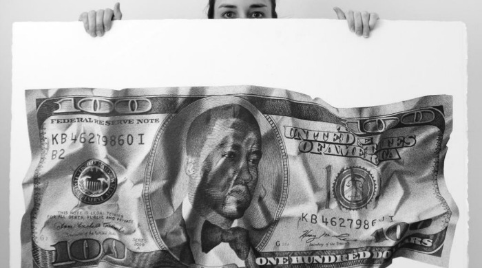 CJ Hendry holding a large pen drawing of Kanye West on a crumpled hundred dollar bill.