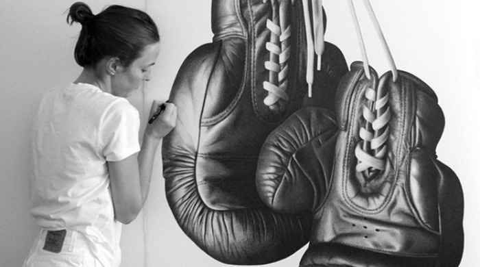 CJ Hendry working on a large pen drawing of boxing gloves.