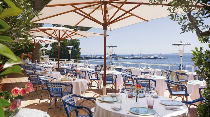 An outdoor dining area by the sea at the Hotel Belles Rives.