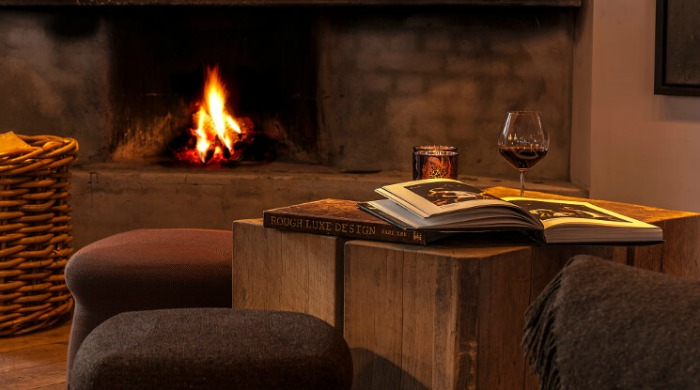 A seating area by an open fire at the Hotel Brosundet.