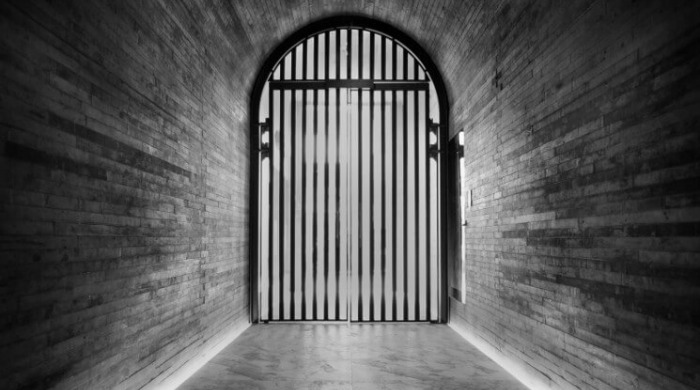 A walkway with a large, barred gate in the Tuve Hotel, Hong Kong.