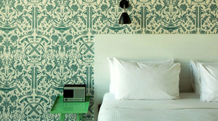 A room in the Wythe Hotel, Brooklyn with intricate green patterned wallpaper.