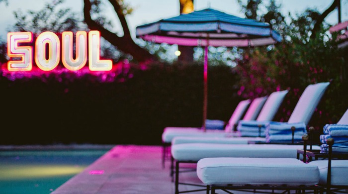 """The pool with a neon """"5OUL"""" sign at the Hotel Saint Cecilia, Austin."""