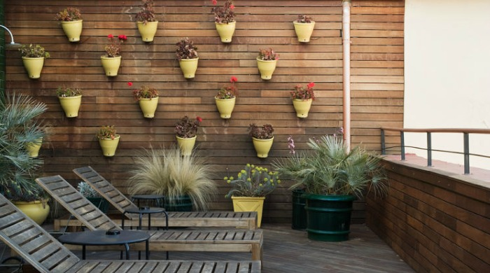 A balcony with yellow flower pots on the wall at the Praktik Metropol, Madrid.