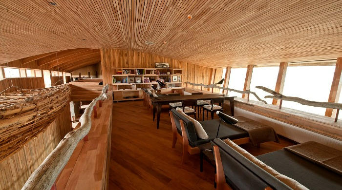 A living area with wooden walls, celiling and floor inside the Tierra Patagonia Hotel & Spa.