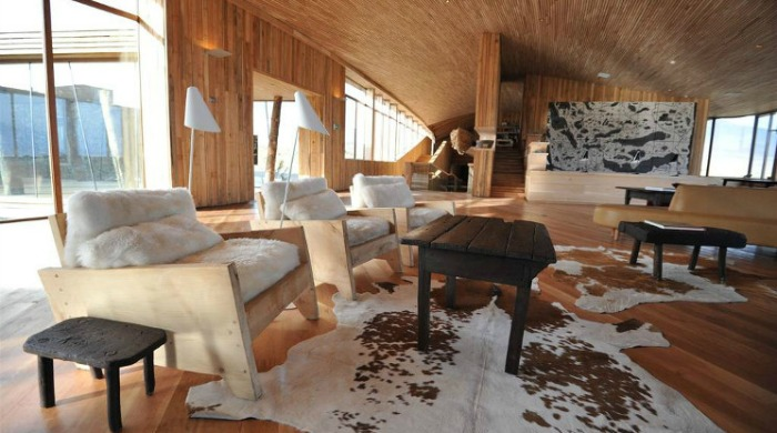 A living area with animal skin rugs inside the Tierra Patagonia Hotel & Spa.