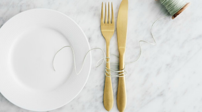 A white plate and gold cutlery on a marble surface.