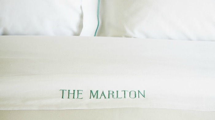 """White sheets embroidered with """"The Marlton""""."""