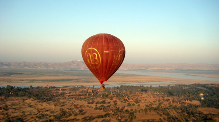 A red hot air balloon travelling over Burma.