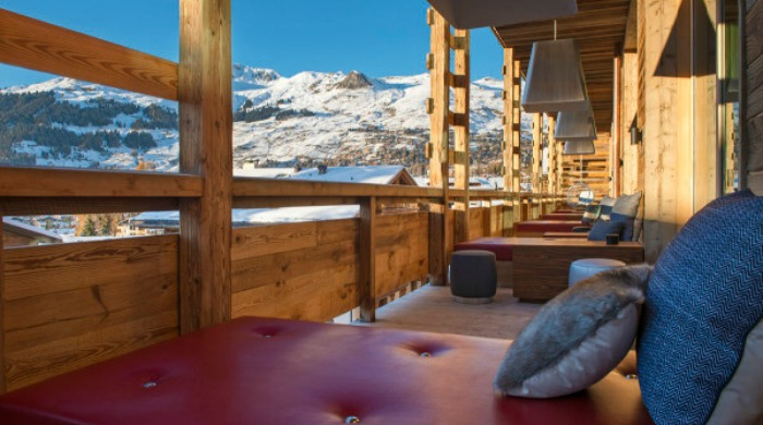An outdoor seating area with a view of the mountains in Hotel W Verbier.