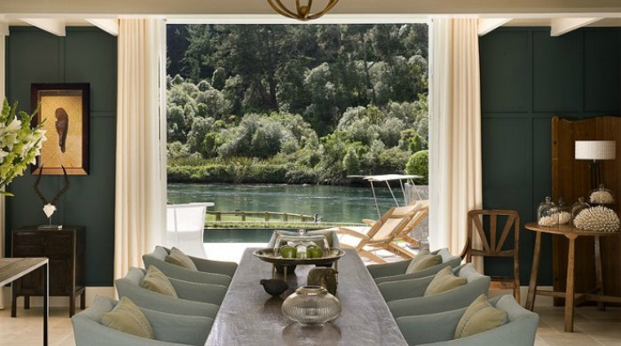 An indoor dining area with views of the lake in Huka Lodge, New Zealand.