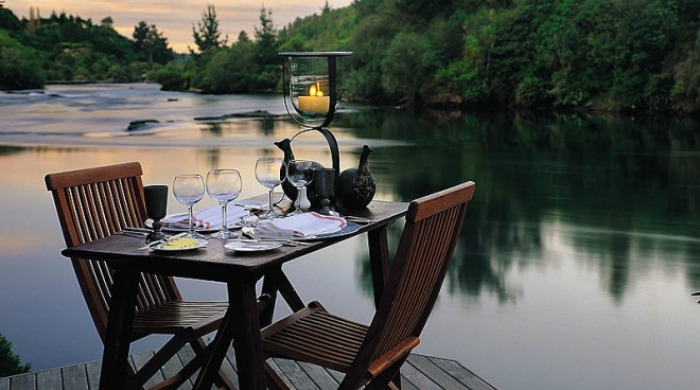An outdoor dining table next to the lake at Huka Lodge, New Zealand.