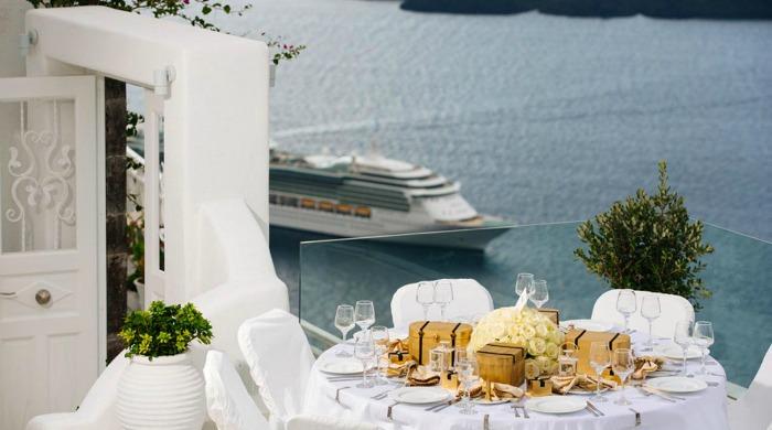 A table on a terrace with views of the ocean at Dana Villas, Santorini.